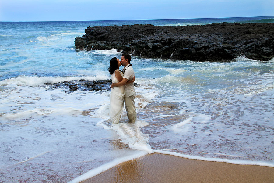 kauai wedding couple standing in ocean kissing