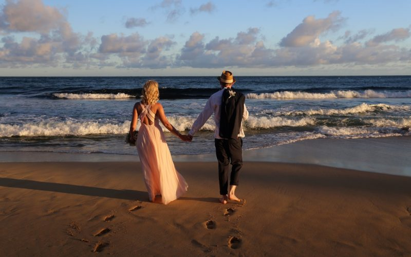 Wedding couple walking away towards the ocean